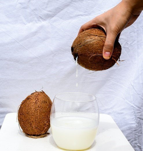 pouring coconut water into a jug