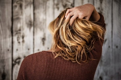 Short Haired Blonde Woman Touching Hair