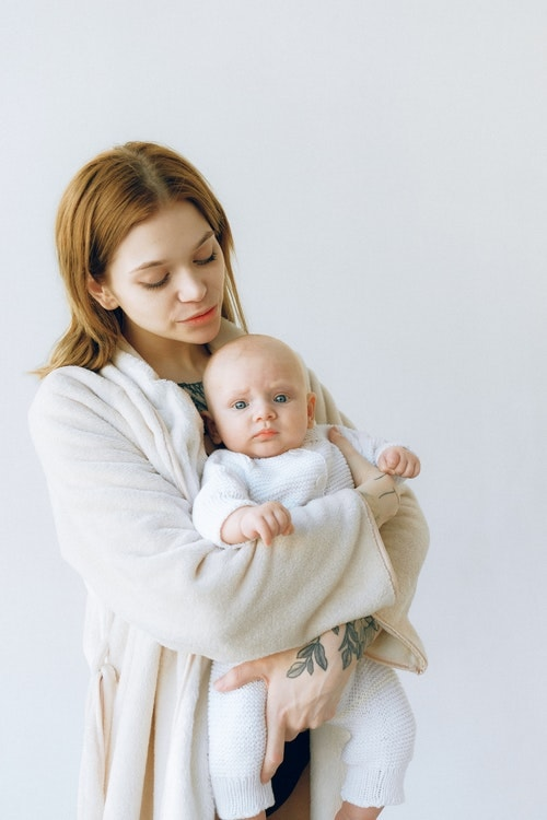 Woman Carrying A Baby Wearing Onesie