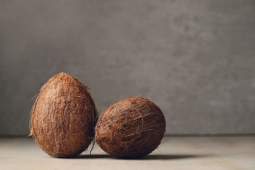 two coconuts on a wooden table