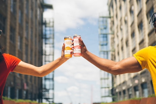 Man and woman holding soda cans